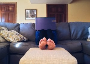 A Person is sitting on the couch with a computer